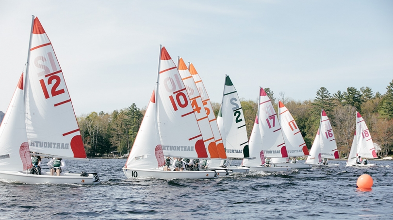 A group of boats sail on Mascoma Lake.