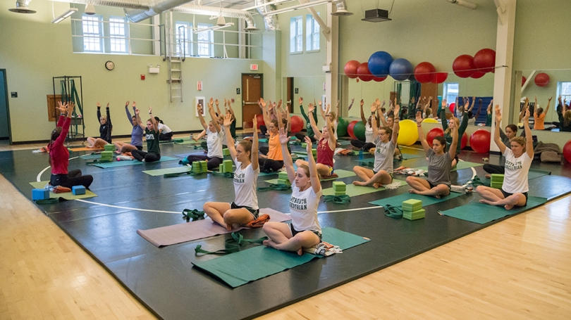 Students participate in a yoga class.